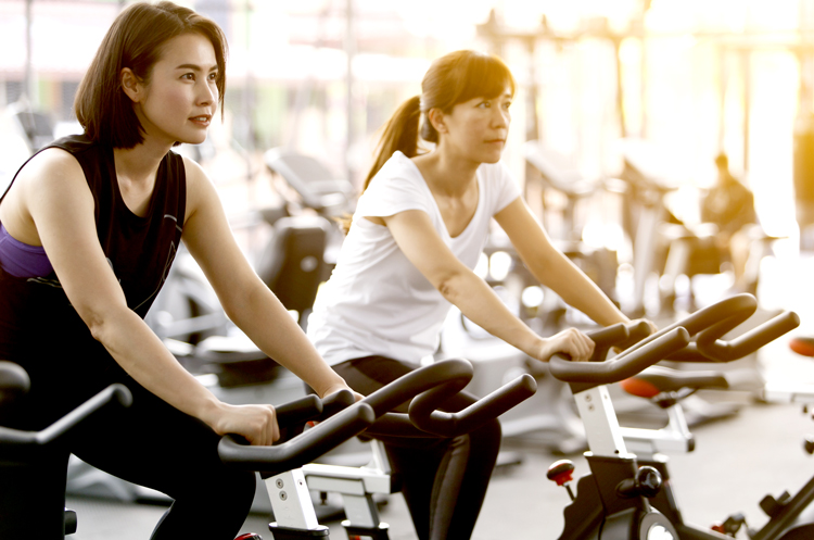 Two women on exercise bikes