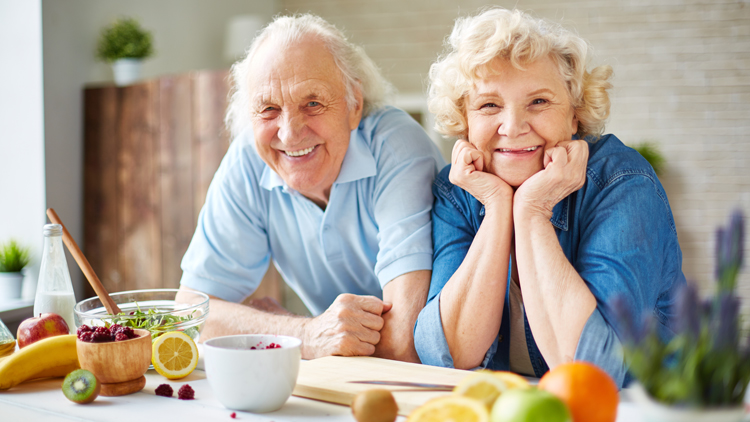 Two elderly people at a counter with food on it