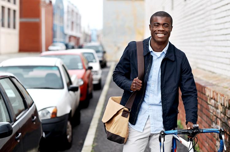 Man walking a bike on a city sidewalk