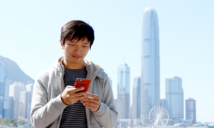 Man on cell phone with cityscape in background