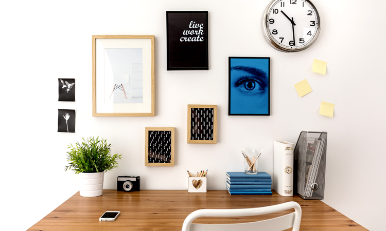 Home-office desk with artwork and supplies