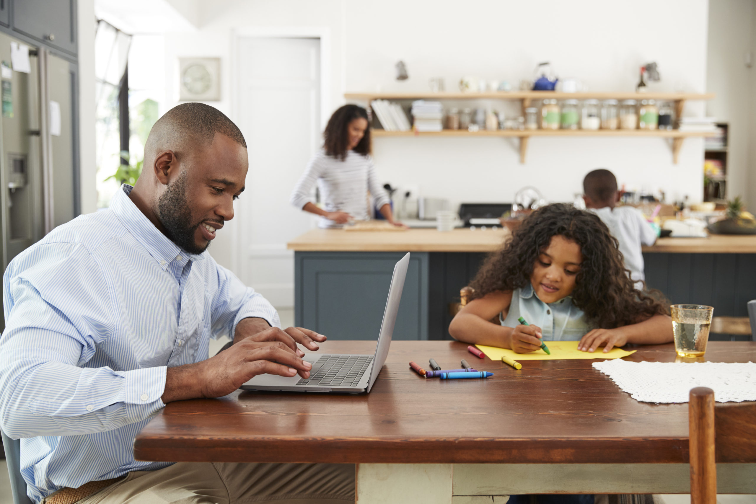 Man working at laptop with family in kitchen