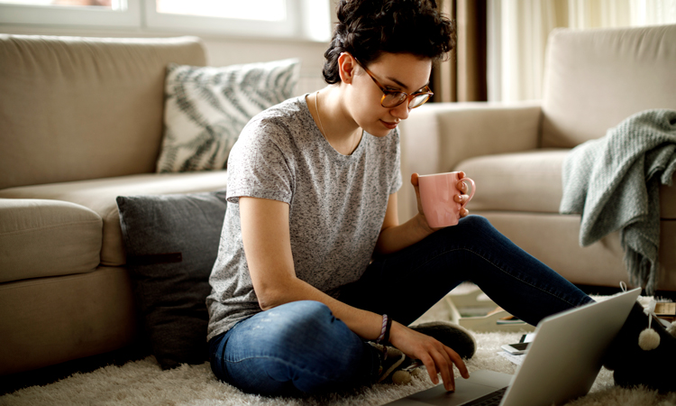 Woman sitting on living room floor with laptop
