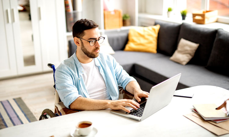 Man in wheelchair works on laptop